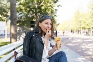 person eating a snack on a bench