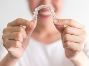 Smiling woman holds Invisalign in Chesapeake aligners in front of her