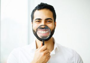 smiling man holding magnifying glass in front of his teeth