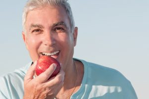 Man with an apple after dental implant surgery in Chesapeake.