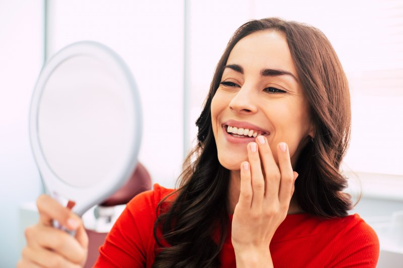 young woman admiring teeth after dental implant surgery Chesapeake